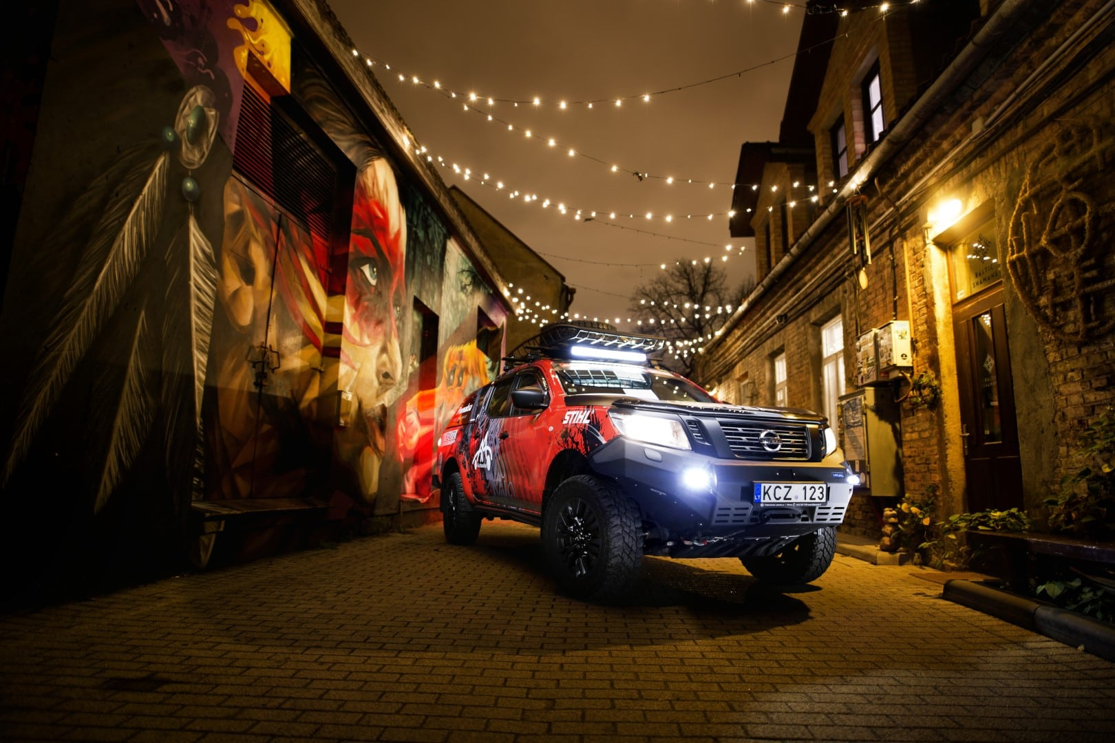 Igo2Dakar Nissan Navara under the Christmas lights next to Shnioka street art piece Giedrius Matulaitis matulaitis.lt